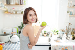 Free Happy Young Asian Woman Eating Green Apple On Kitchen. Diet. Stock Image - 75665061