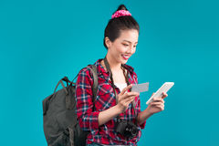 Happy young asian woman holding credit card and smartphone stand Royalty Free Stock Photo