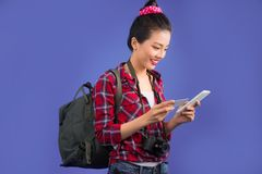 Happy young asian woman holding credit card and smartphone standing over blue stock photo