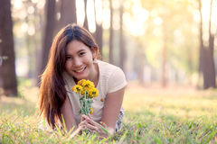 Happy young asian woman holding flower and lying down on grass royalty free stock photography