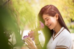 Happy young asian woman holding orchid with a happy smile in graden.  royalty free stock images