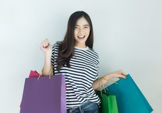Happy young asian woman holding shopping bags. Online shopping and browsing concept.  royalty free stock image