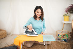 Happy young asian woman ironing clothes sitting on floor at home Stock Image