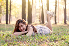 Happy young asian woman lying down on grass in the park royalty free stock image