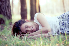 Happy young asian woman lying down on grass stock photos