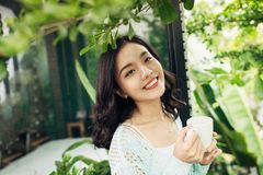 Happy young asian woman with mug in hands drinking coffee standi Royalty Free Stock Image