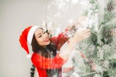 Happy young asian woman near christmas tree celebrating New Yea