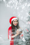 Happy young asian woman opening shopping bag near christmas tree.  Royalty Free Stock Image