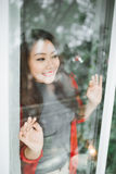 Happy young asian woman opening shopping bag near christmas tree Royalty Free Stock Photography