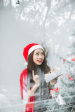 Happy young asian woman opening shopping bag near christmas tree.  Stock Photography