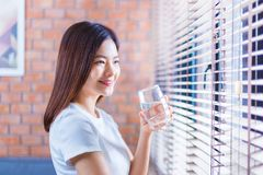 Happy young asian woman relaxing at home holding a cold glass of. Happy young asian woman casually relaxing by her living room window at home holding a cold Stock Photos