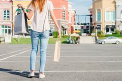 Happy young Asian woman shopping an outdoor market with a background of pastel buildings and blue sky. Young woman smile with a colorful bag in her hand Royalty Free Stock Photo