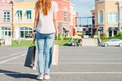 Happy young Asian woman shopping an outdoor market with a background of pastel buildings and blue sky. Young woman smile with a colorful bag in her hand Stock Image