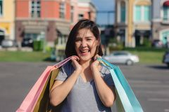 Asian woman shopping an outdoor market with background of pastel buildings and blue sky. Happy young Asian woman shopping an outdoor market with background of Royalty Free Stock Photography