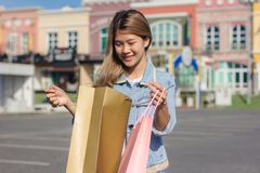 Happy young Asian woman shopping an outdoor market with background of pastel buildings and blue sky. Young asian woman smile with a colorful bag in her hand Stock Photography
