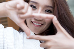 Happy young Asian Woman showing frame finger sign Royalty Free Stock Images