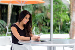 Happy young Asian woman sitting at outdoor cafe table reading te Stock Photo
