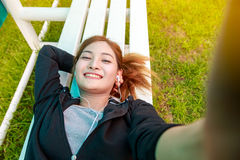 Happy young asian woman smiling and taking selfie in the park Royalty Free Stock Photos