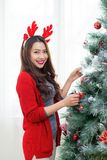 Happy young asian woman  standing near christmas tree at home ce Royalty Free Stock Images