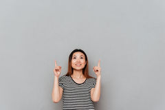 Happy young asian woman standing over grey wall pointing Stock Photos