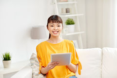 Happy young asian woman with tablet pc at home Stock Image