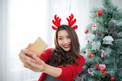 Happy young asian woman  taking a selfie photo near christmas tr. Ee at home celebrating New Year Royalty Free Stock Images