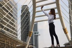 Happy young Asian woman taking a selfie photo at urban building with copy space background royalty free stock image