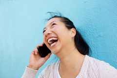Happy young asian woman talking on mobile phone against blue wall Royalty Free Stock Photography