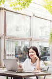 Happy young asian woman thinking and enjoying her coffee while u Royalty Free Stock Photos