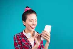 Happy young asian woman using smartphone standing over blue. Royalty Free Stock Photos