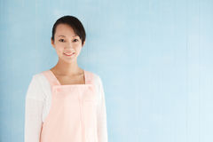 Happy young asian woman wearing an apron Stock Photos