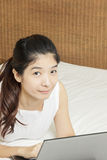 Happy young asian woman working with laptop in bedroom Royalty Free Stock Photos
