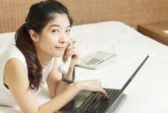 Happy young asian woman working on phone and laptop in bedroom Stock Photos