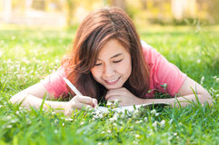 Happy Young Asian Woman Writing in Notebook and Smiling Stock Images