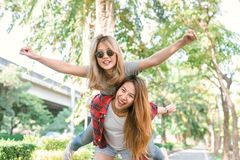 Happy young asian women couple playing to each other while they do city trip in warm sunlight morning weekend. City and nature lifestyle of Young women Stock Photography