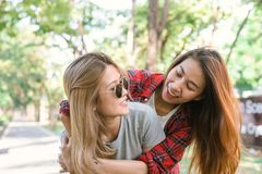 Happy young asian women couple playing to each other while they do city trip in warm sunlight morning weekend. City and nature lifestyle of Young women Royalty Free Stock Images