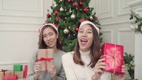 Happy young Asian women giving christmas gifts to each other in her living room at home in Christmas Festival. stock video