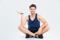 Happy young athletic man sitting and holding copyspace on palm Stock Photography