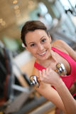 Happy young athletic woman lifting weights Stock Image
