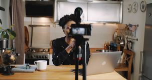 Happy young attractive African video blogger recording new vlog using professional camera at home kitchen slow motion. Blogging and vlogging as a creative stock video footage