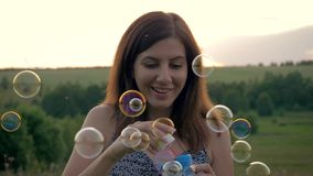 Funny Young Woman Blowing Lots Of Soap Bubbles At Sunset stock video footage