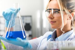 Young attractive female scientist holding a flask with blue liqu Royalty Free Stock Photo