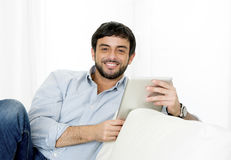 Happy Young attractive Hispanic man at home on white couch using digital tablet or pad Stock Image