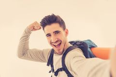 Happy young attractive tourist student with backpack taking a selfie in traveling and connections royalty free stock image
