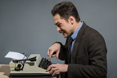 Happy young author typing at typewriter Stock Image