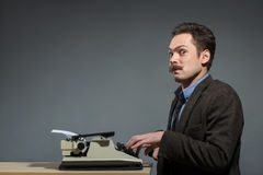 Happy young author typing at typewriter Stock Photography