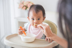 Happy Young Baby In High Chair being fed. Portrait Of Happy Young Baby In High Chair being fed by mum Stock Image