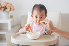 Happy Young Baby In High Chair being fed Royalty Free Stock Photos