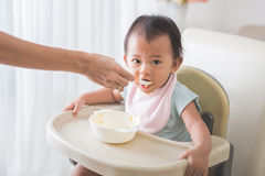 Happy Young Baby In High Chair being fed Royalty Free Stock Images