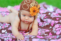 Happy young baby is sitting on green grass outside with bright Royalty Free Stock Photo